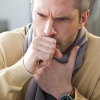 Man with whooping cough feeling sick with a scarf on