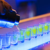 Shot glasses being poured on a bar