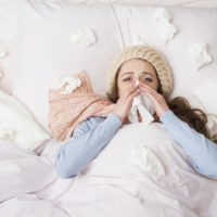 Sick woman lying in bed with high fever due to the swine flu