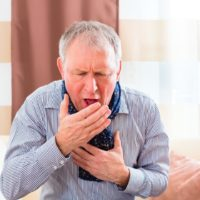 Senior gentleman violently coughing due to the whooping cough