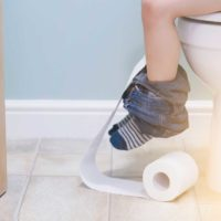 child's legs dangle from toilet